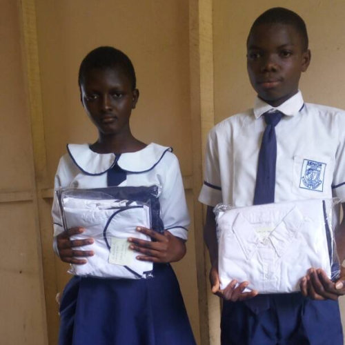 two students holding new school uniform